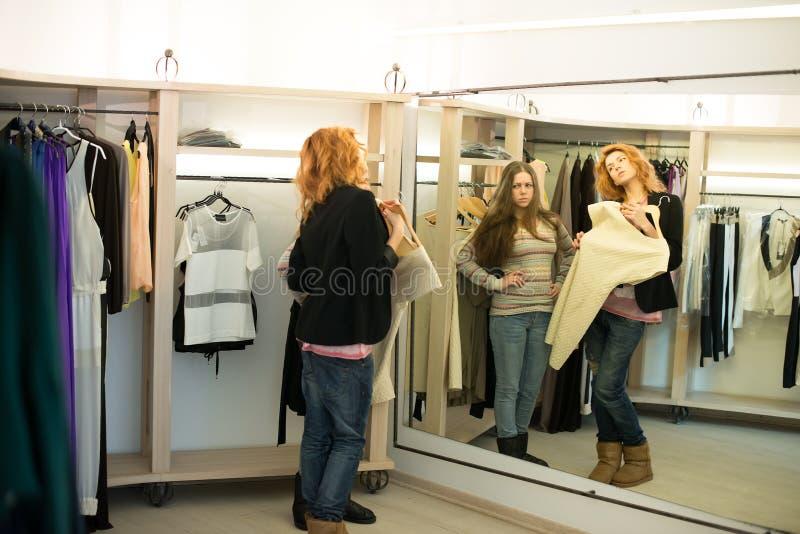 Fraueneinkaufen, welches die Kleider schauen im Spiegel unsicher wählt stockbilder