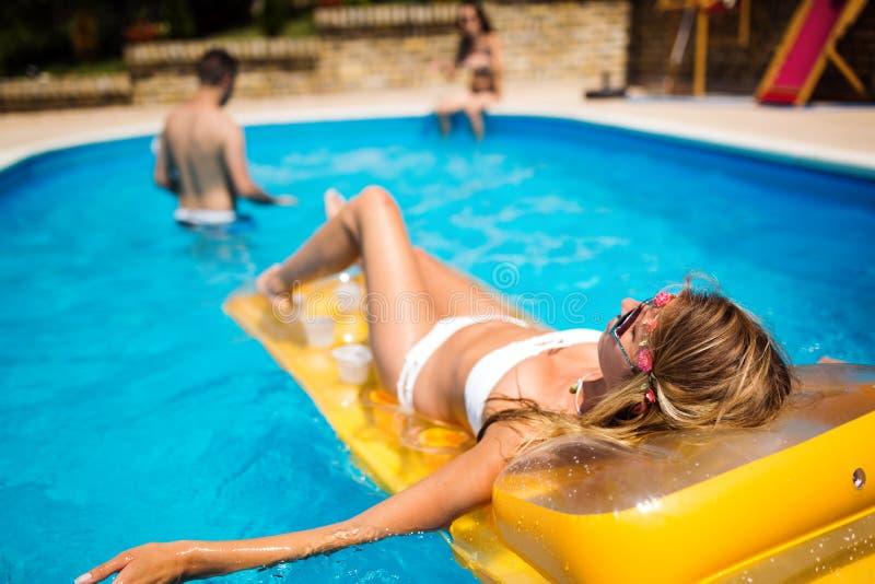 Frauenentspannung und -Sonnenbräunung durch den Swimmingpool stockfotografie