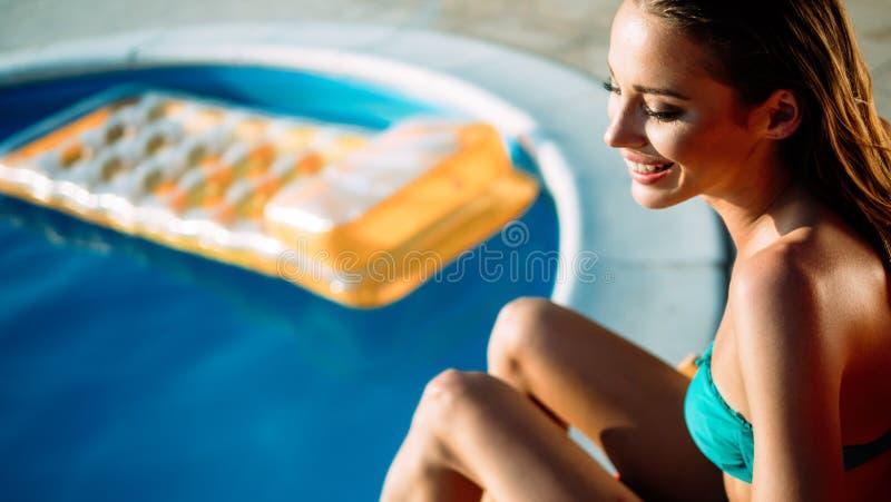 Frauenentspannung und -Sonnenbräunung durch den Swimmingpool stockfoto