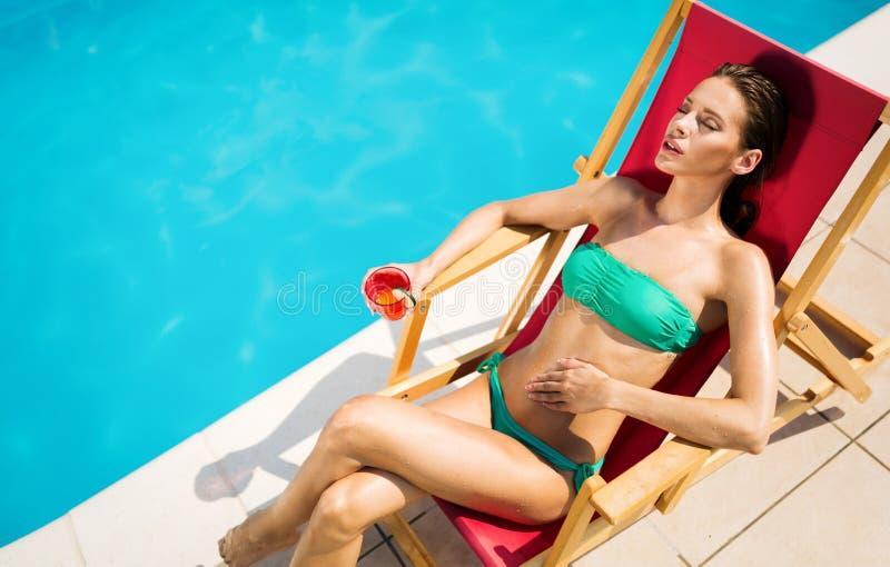 Frauenentspannung und -Sonnenbr?unung durch den Swimmingpool lizenzfreies stockbild