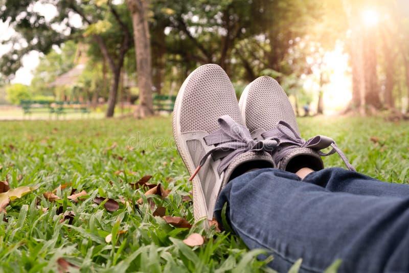 Frauenfüße im Turnschuh auf grünem Gras im Park lizenzfreie stockbilder