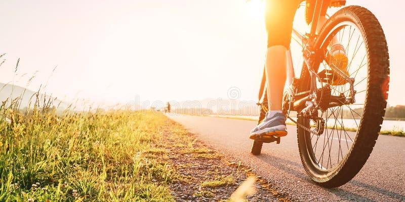 Frauenfüße auf bycikle eln in Sonnenunterganglicht rad stockfoto