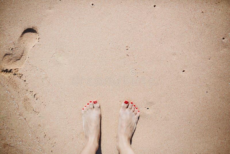 Frauenfüße auf sandigem Strand Glücklicher Mann genießt an den Feiertagen in dem Meer lizenzfreies stockbild