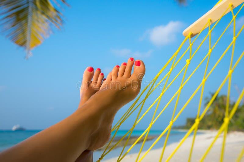 Frauenfüße in der Hängematte auf dem Strand lizenzfreie stockbilder