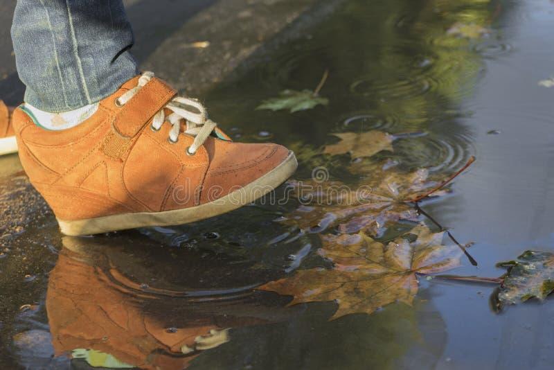 Frauenfüße, die in eine Pfütze in den orange Stiefeln gehen stockbilder