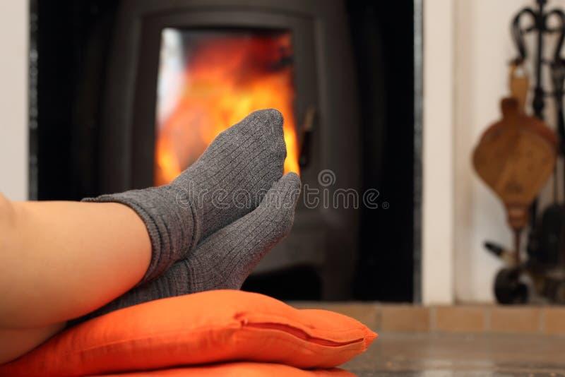 Frauenfüße mit den Socken, die nahe Feuerplatz stillstehen lizenzfreie stockfotografie