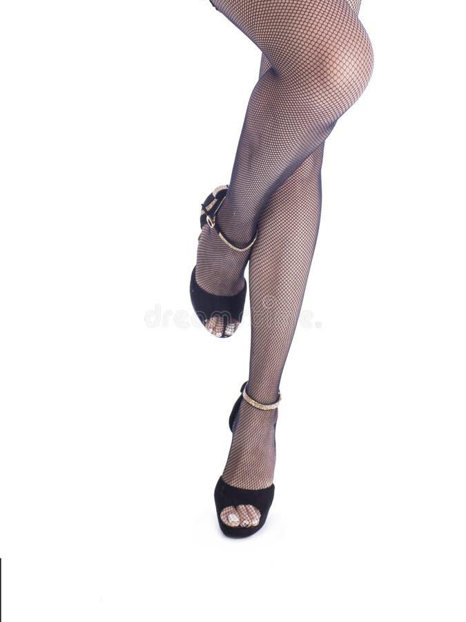 Frauenfüße mit schwarzen hohen Absätzen und Fischnetzstrumpfhosen lizenzfreie stockbilder