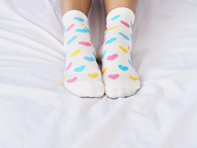 Frauenfüße weiße Socke mit Pastellherzformmuster tragend stockfoto