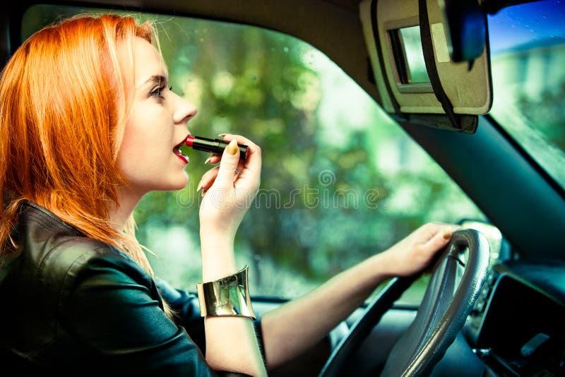 Frauenfahrer, der ihre Lippen während Autofahren malt stockbild