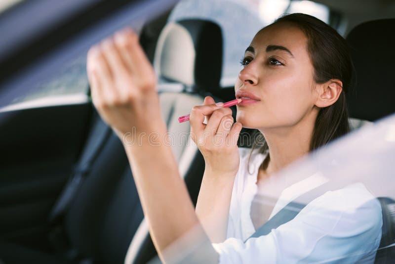 Frauenfahrer, der Rückspiegel betrachtet und das Make-up beim Fahren des Autos korrigiert lizenzfreie stockbilder