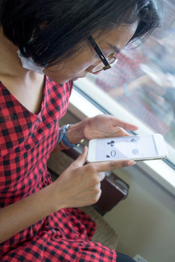 Frauenfahrten auf Zug und Blicke auf Smartphone lizenzfreie stockbilder