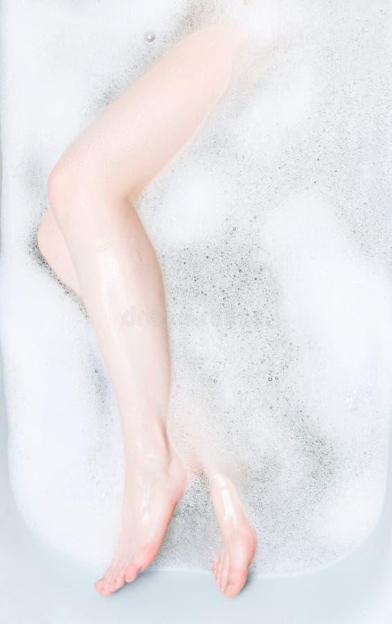 Frauenfahrwerkbeine im Bad mit Schaumgummi lizenzfreie stockbilder