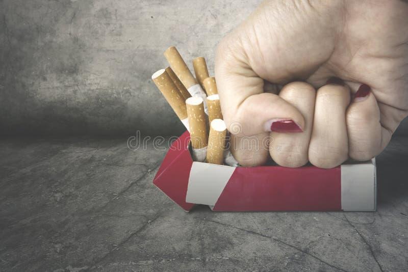 Frauenfaust, die Zigaretten zerquetscht lizenzfreies stockbild