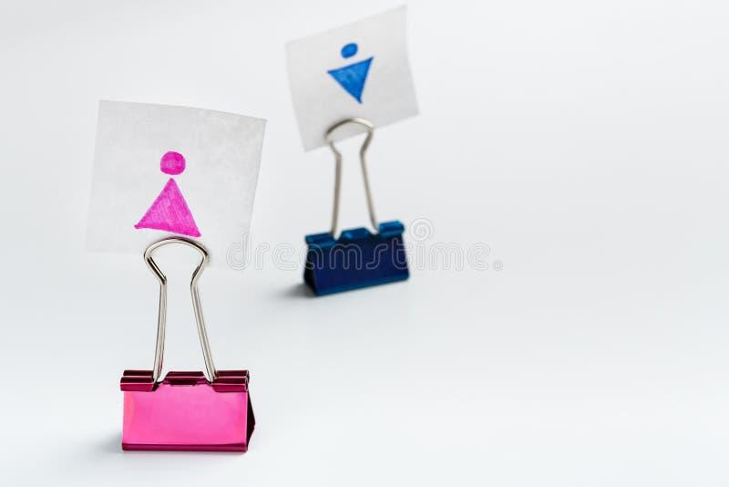 Frauenfigur auf führendem Mann des rosa Mappenclips lizenzfreie stockfotos