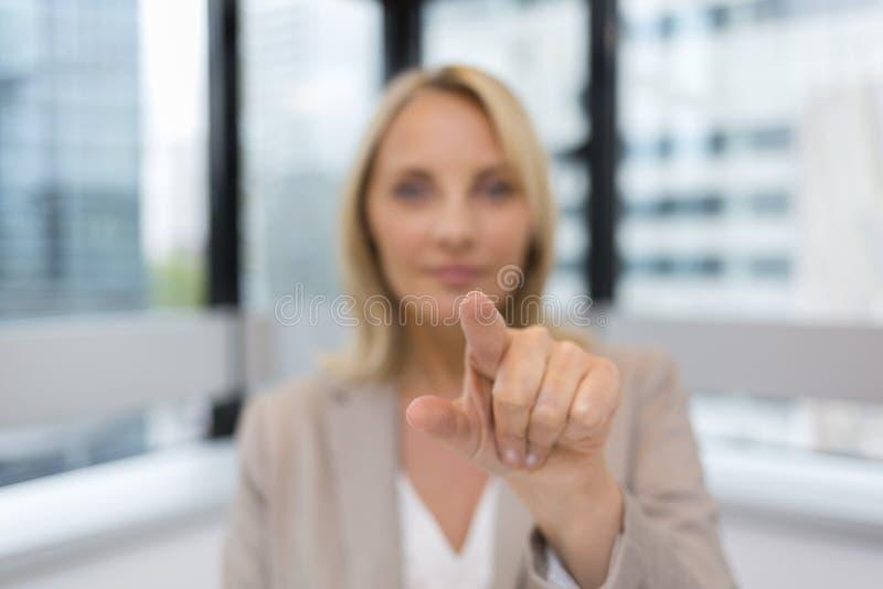 Frauenfinger, der einen digitalen Schirm drückt Bürohintergrund lizenzfreies stockfoto