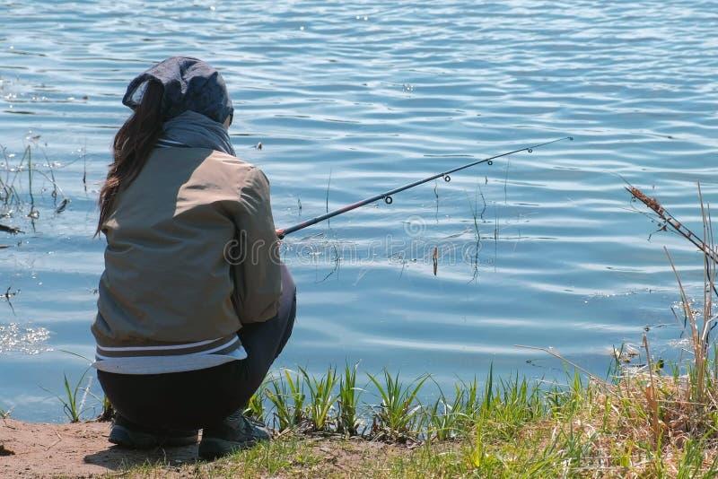 Frauenfischen auf dem Teich an einem warmen Frühlingstag stockfotos