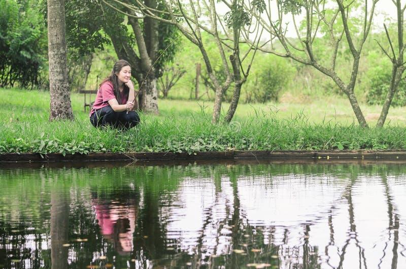 Frauenfischen und -entspannung, geduckt vor einem See, halten lizenzfreie stockbilder