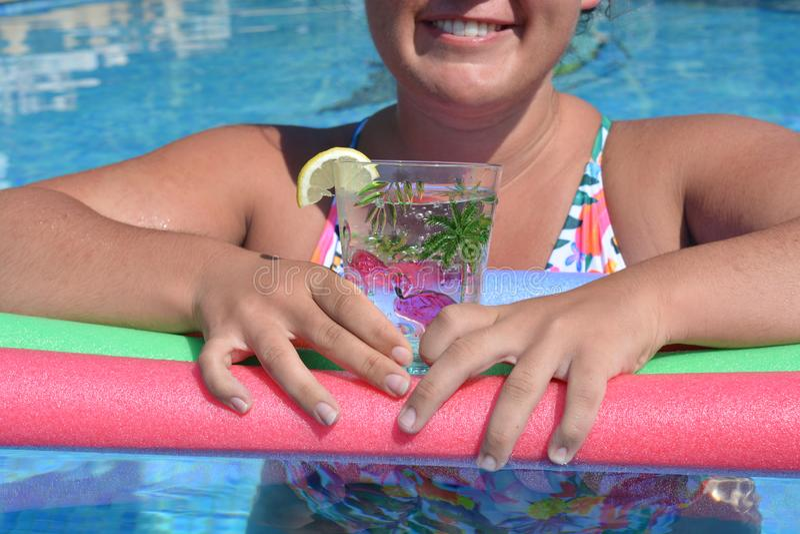 Frauenfreien, Glas funkelndes Wasser in einer Plastikschale halten stockfotografie