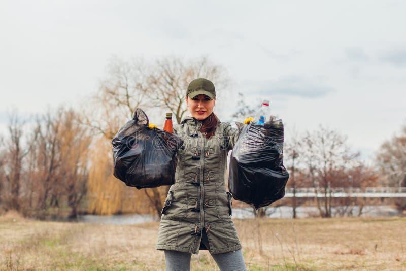Frauenfreiwilliger r?umte den Abfall im Park auf Leute hoben Abfall und Darstellenergebnis mit vollen Taschen auf ?kologie lizenzfreie stockfotos