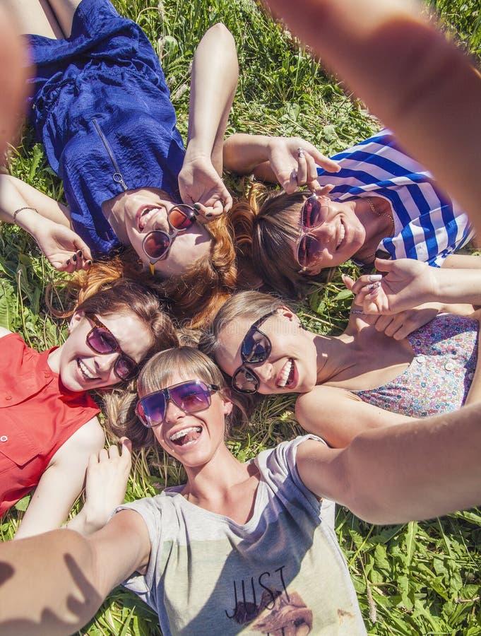 Frauenfreundinlachen, das ein selfie liegt auf dem Gras nimmt stockbilder