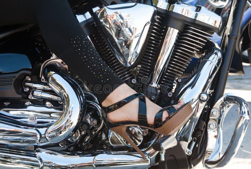 Frauenfuß auf einem Motorradmotor stockbild