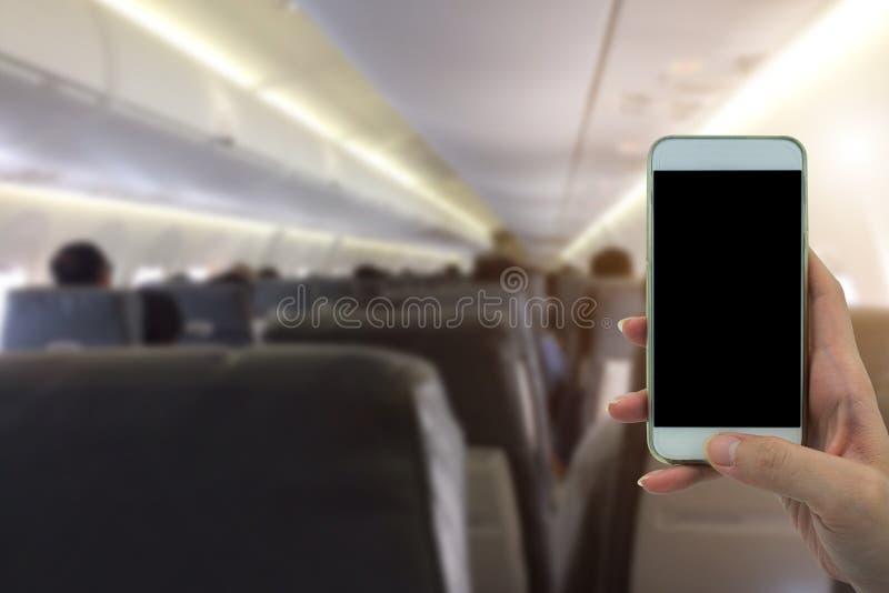 Frauengebrauch Ihr Telefon im Flugzeug verwischte Hintergrund stockbilder