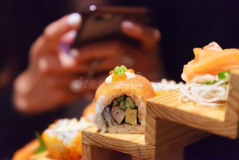 Frauengebrauch Smartphone machen Foto auf japanischem neuem Fischfutter, Salmon Sushi Rolls Assortment, der herein auf hölzernen  stockfoto