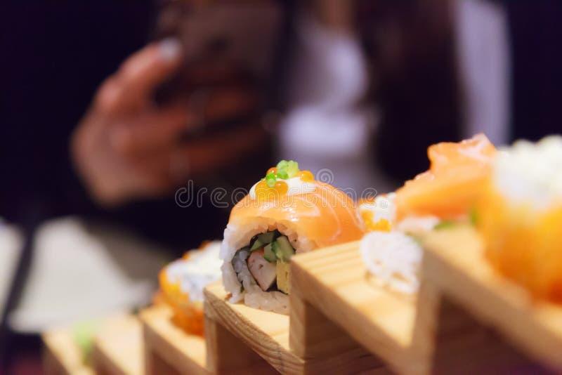 Frauengebrauch Smartphone machen Foto auf japanischem neuem Fischfutter, Salmon Sushi Rolls Assortment, der herein auf hölzernen  stockbild
