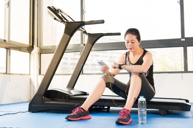 Frauengebrauch smartwatch Kontrollpulsschlag des Sports asiatisches hörendes musi lizenzfreie stockbilder