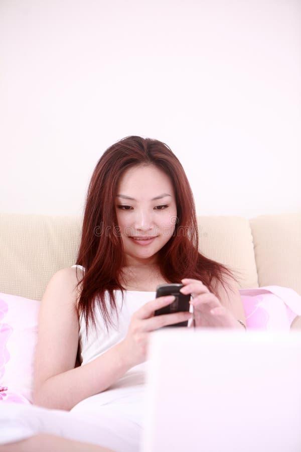 Frauengebrauchlaptop auf Bett stockfotos