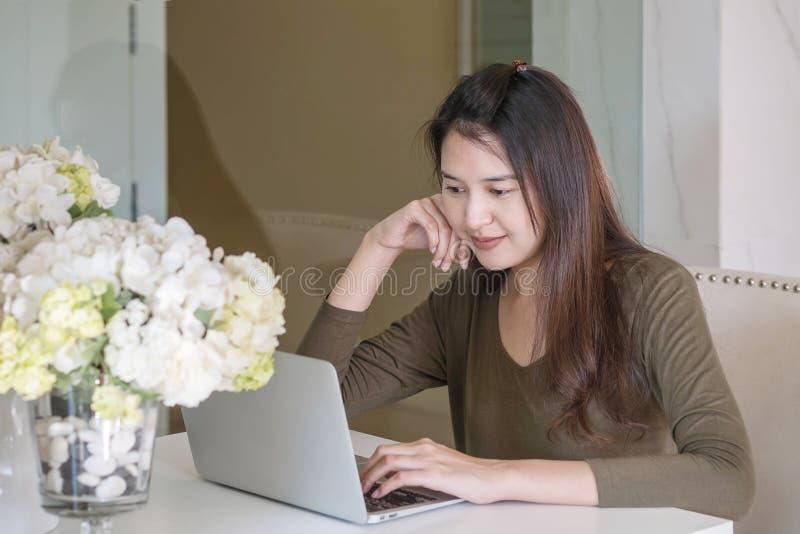 Frauengebrauchs-Computernotizbuch der Nahaufnahme asiatisches im Raum mit glücklichem Gesichtsgefühl unter Fensterlicht im Lebens stockbild