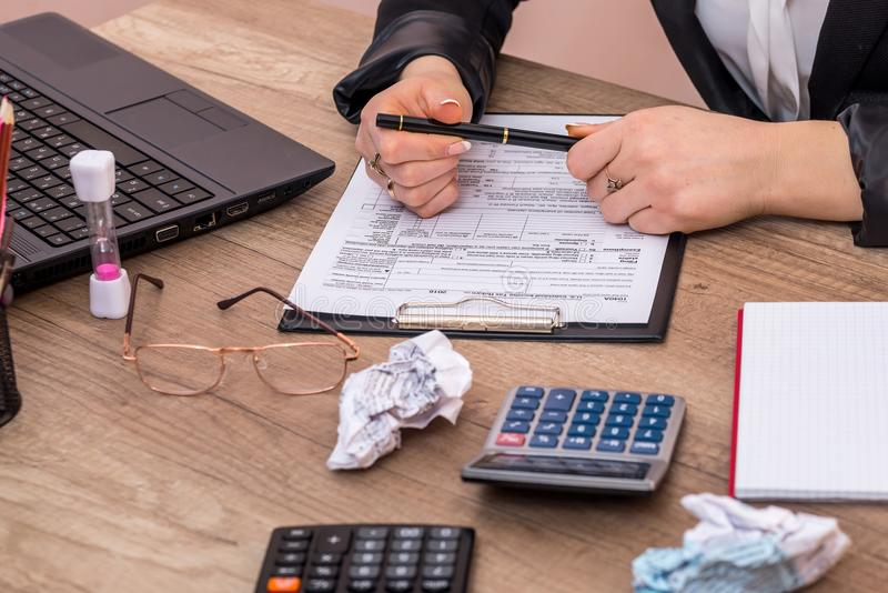 Frauengebrauchstaschenrechner mit Laptop für das Füllen des 1040 Steuerformulars lizenzfreies stockbild