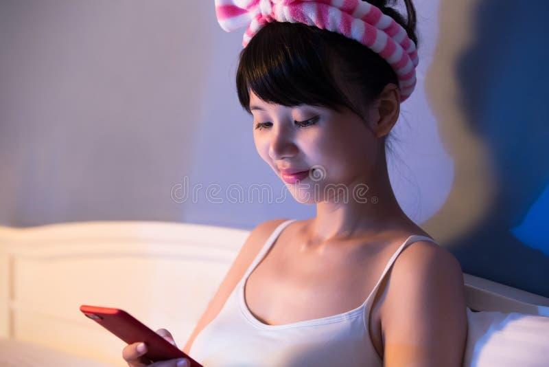 Frauengebrauchstelefon auf Bett lizenzfreie stockfotografie