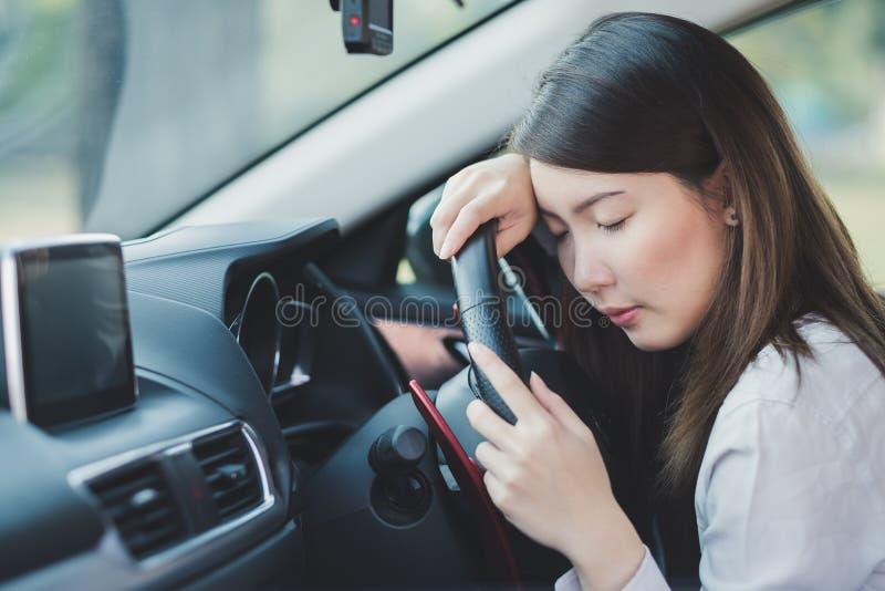 Frauengefühl, das versucht wird und auf einem Auto geschlafen ist stockfotografie