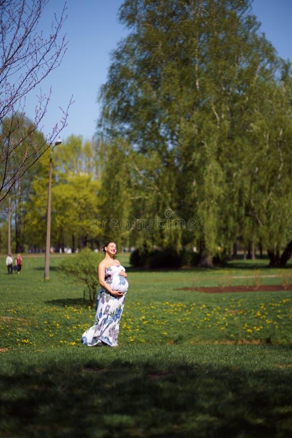 Frauengehen, -betrieb des jungen Reisenden genießt das schwangere, herum drehend und ihre Freizeitfreizeit in einem Park mit stockbilder