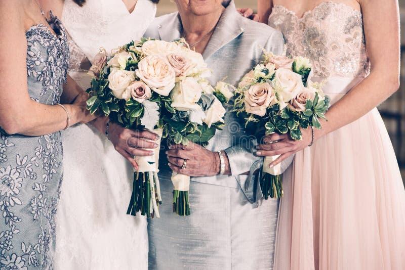 Frauengenerationsfamilie und -braut, die Blumenbündel am Hochzeitstag halten lizenzfreie stockfotografie