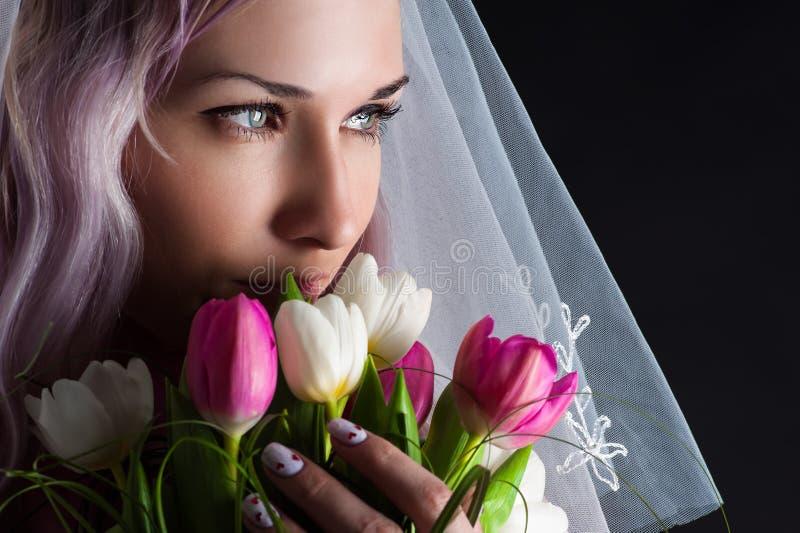 Frauengesicht mit einem Blumenstrauß von Tulpen stockfoto
