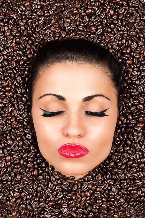 Frauengesicht mit geschlossenen Augen in den Kaffeebohnen lizenzfreie stockfotografie