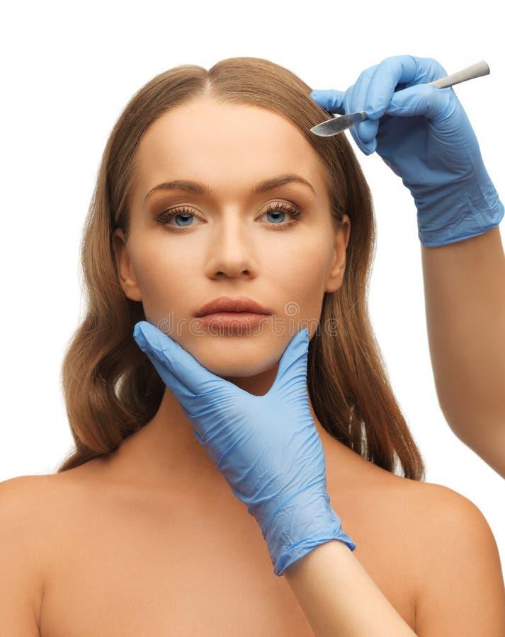 Frauengesichts- und -Kosmetikerhände lizenzfreie stockbilder