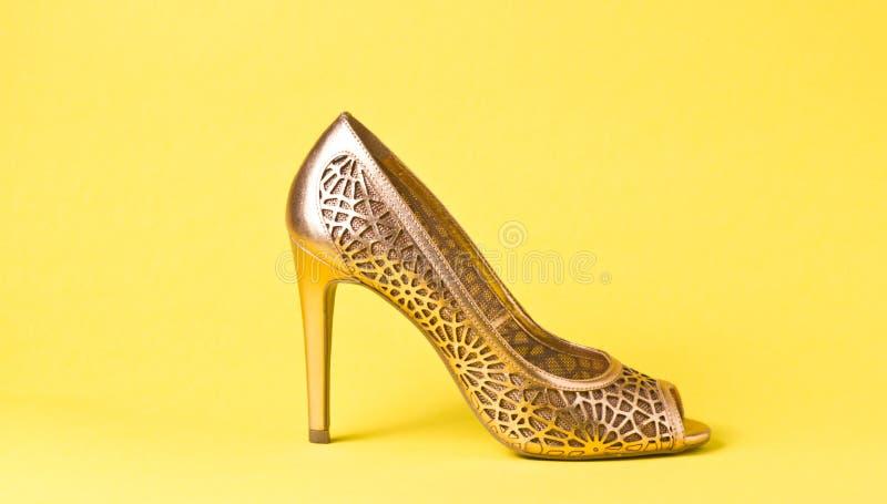 Frauengoldschuhe auf Hintergrund stockfotos