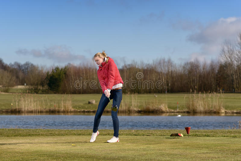 Frauengolfspieler, der den Golfball schlägt stockfotografie