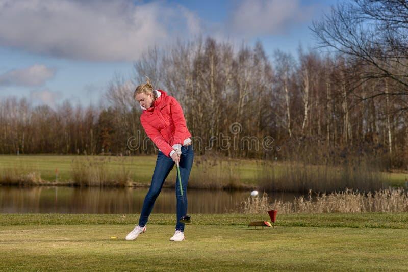 Frauengolfspieler, der den Golfball schlägt stockfoto