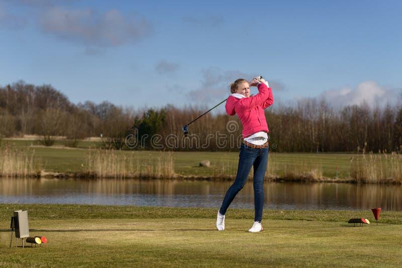 Frauengolfspieler, der einen Golfball auf der Fahrrinne schlägt lizenzfreies stockbild