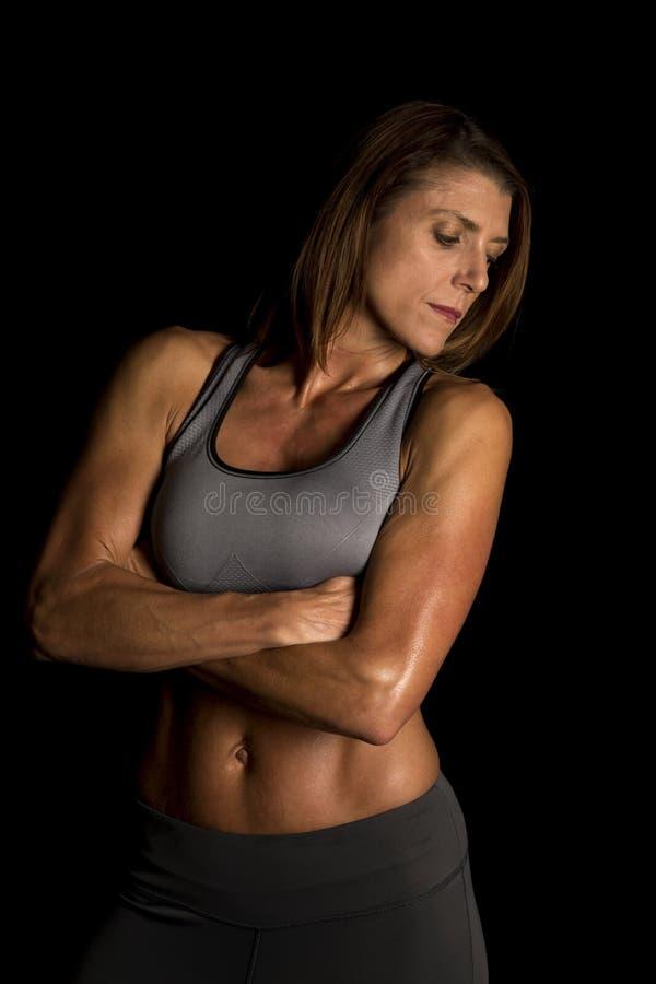 Frauengrau-Sport-BH auf den schwarzen gefalteten Armen schauen unten lizenzfreie stockfotos