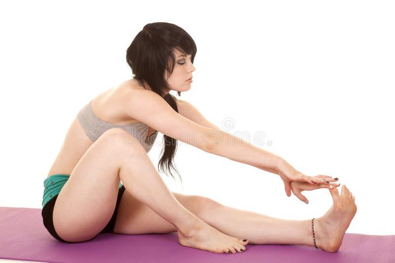 Frauengrau-Sport-BH sitzen Ausdehnungsbeine stockfoto