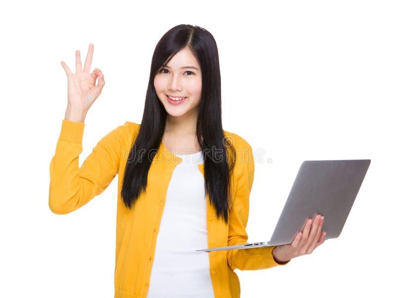 Frauengriff mit Laptop und okayzeichen stockbild