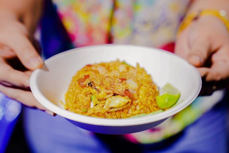 Frauengriff-Papierteller mit Tom-yum kung Innere gebratenen Reises am Nahrungsmittel-LKW - Stra?ennahrungsmittelereignis in Thail lizenzfreies stockfoto