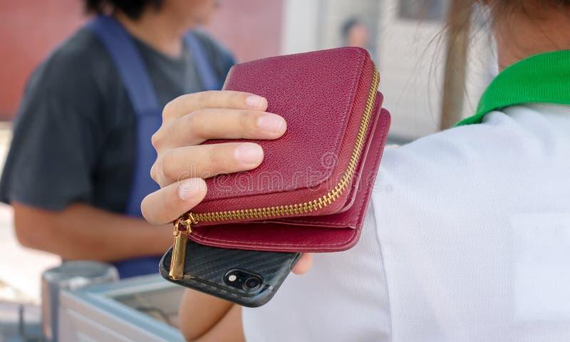 Frauengriffe Geldbörse und Smartphone über der Schulter ahnungslos von der Gefahr von Handtaschendieben lizenzfreies stockfoto