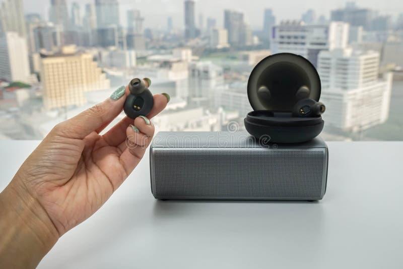 Frauengriffschwarzes bluetooth Kopfhörer in der Hand, zum mit modernem drahtlosem Sprecher zusammenzupassen lizenzfreies stockfoto