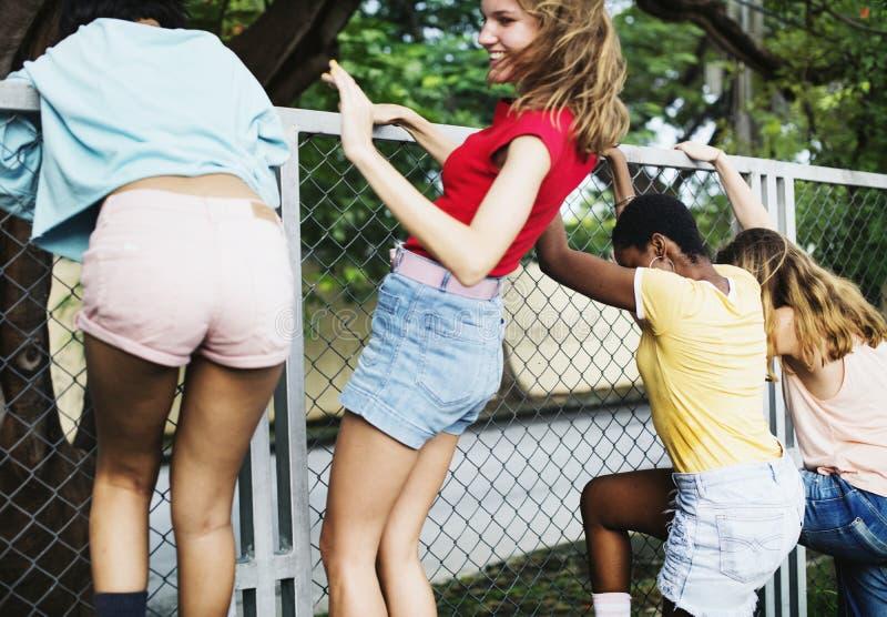 Frauengruppe, die den Zaun klettert stockbild